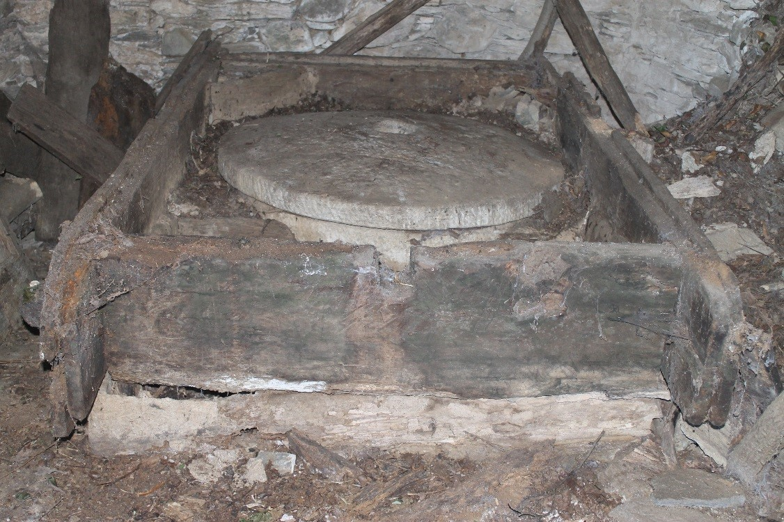 Voilà le mécanisme qui permettait au moulin de fonctionner. Les cuillères en bois était insérer dans la roue en bois ces dernières ont aujourd'hui disparues. On peut voir derrière une colonne en bois, il s'agit de la colonne forcée qui projetait avec beaucoup de force, l'eau sur les palettes en bois (les cuillères) pour faire tourner les meules en pierre situées à l'étage supérieur.